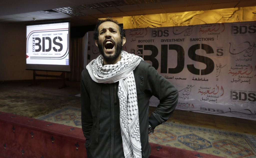 FILE - In this April 20, 2015, file photo, an Egyptian man shouts anti-Israeli slogans in front of banners with the Boycott, Divestment and Sanctions (BDS) logo during the launch of the Egyptian campaign that urges boycott, divestment and sanctions against Israel and Israeli-made goods, at the Egyptian Journalists' Syndicate in Cairo, Egypt. Israel is using its world-leading expertise in cyber security to take on the growing threat posed by the global pro-Palestinian movement to boycott Israel. (AP Photo/Amr Nabil, File)