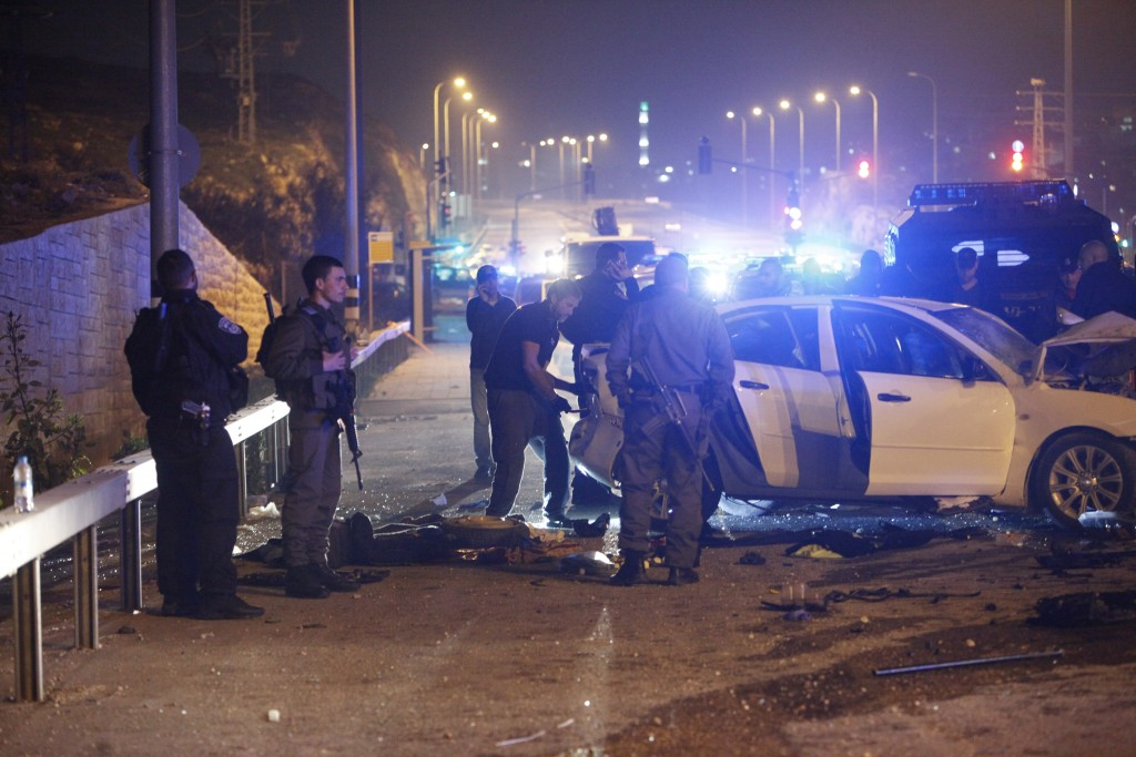 Israeli police stand at the scene of an alleged car ramming attack near Jerusalem, Saturday, Feb. 13, 2016. Police said a Palestinian purposely ploughed his vehicle into a group of police officers injuring three of them lightly. The officers opened fire wounding the three Palestinians in the vehicle. (AP Photo/Mahmoud Illean)