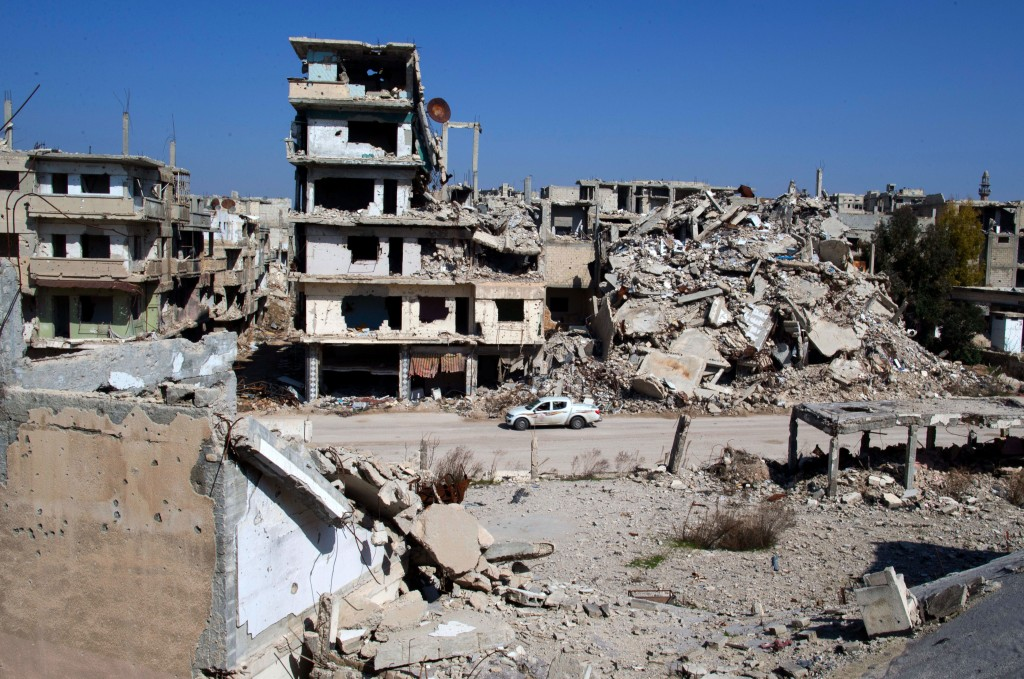 """In this picture taken Friday, Feb. 26, 2016, a car drives through a devastated part of the old city of Homs, Syria. Some 1,200 rebels and civilians, many of them wounded and starving from a yearlong siege, withdrew from the last remaining strongholds in the ancient heart of Homs in May 2014, surrendering to President Bashar Assad a bloodstained city once dubbed the """"capital of the revolution."""" (AP Photo/Hassan Ammar)"""