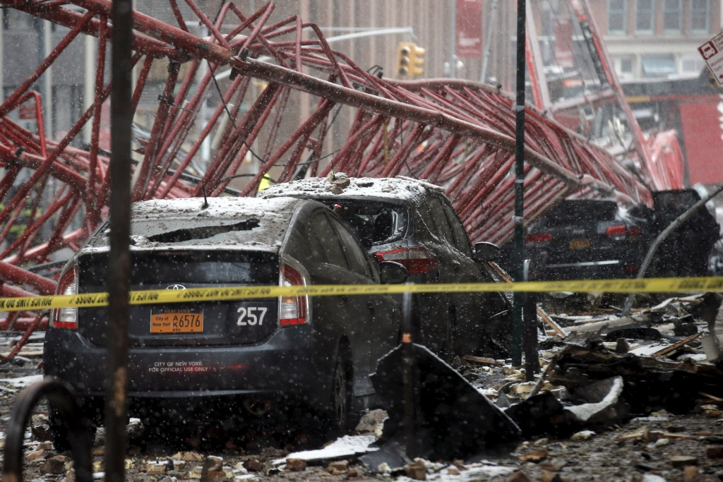 A construction crane is seen on top of cars along the street in downtown Manhattan in New York, February 5, 2016. The construction crane collapsed in lower Manhattan during a swirling snowstorm on Friday, killing one person and crushing parked cars in the first accident of its kind in New York City since 2008. REUTERS/Brendan McDermid