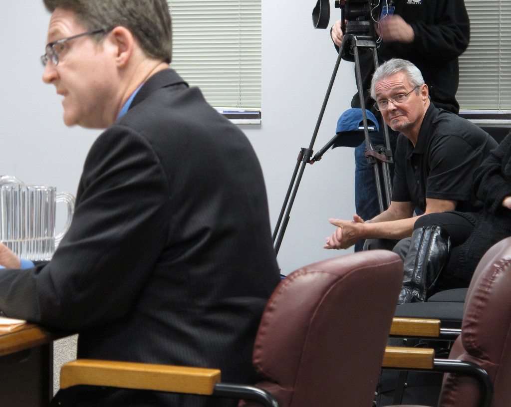 Richard Flynt, right, a son of 1957 manslaughter victim Eugene Flynt, watches from the audience as the Summit County, Ohio, prosecutor's chief counsel, Brad Gessner, left, argues against parole for former fugitive Frank Freshwaters, shortly before the full state parole board granted parole for Freshwaters during a hearing in Columbus, Ohio, on Thursday. (AP Photo/Kantele Franko)