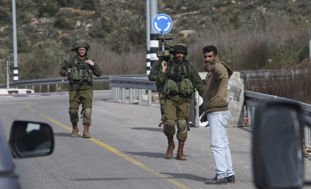 Israeli soldiers inspect a Palestinian man at an Israeli checkpoint leading to the West Bank city of Ramallah February 1, 2016. REUTERS/Mohamad Torokman