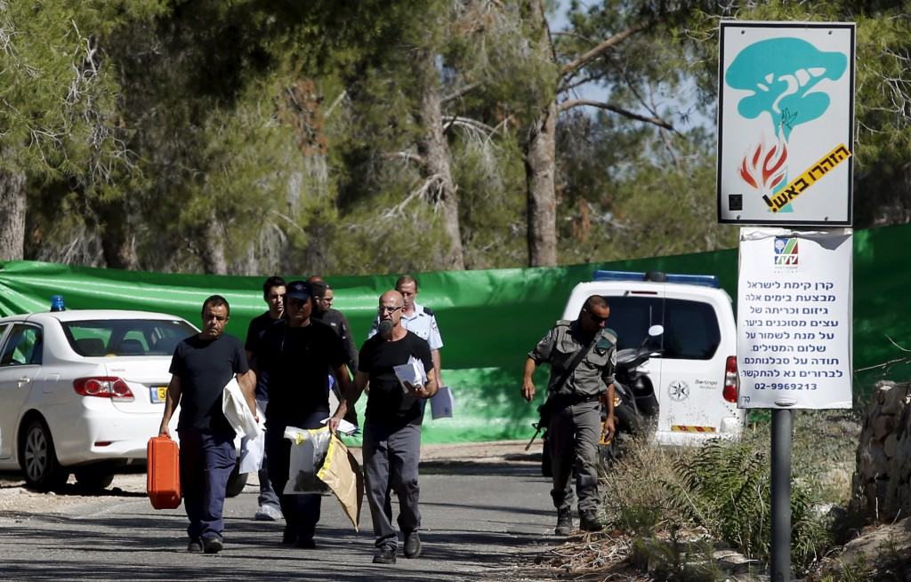 Israeli police investigators carry evidence from the scene where the body of 16-year-old Palestinian Mohammed Abu Khudair was found in the Jerusalem Forest, in this July 2, 2014 file photo. REUTERS/Ronen Zvulun/Files