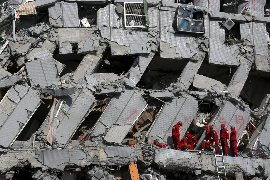 Rescue personnel work at the site where a 17-storey apartment building collapsed after an earthquake hit Tainan, southern Taiwan February 7, 2016. REUTERS/Tyrone Siu TPX IMAGES OF THE DAY