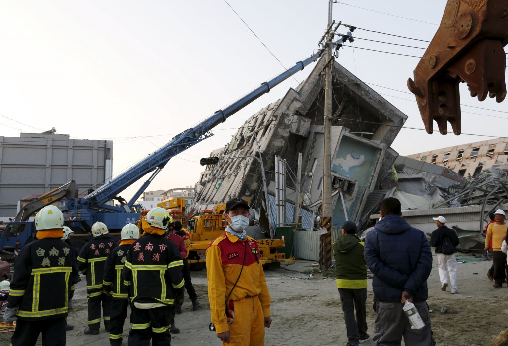 Rescue workers stand in front of a 17-storey apartment building which collapsed after an earthquake hit Tainan, southern Taiwan February 7, 2016. REUTERS/Tyrone Siu