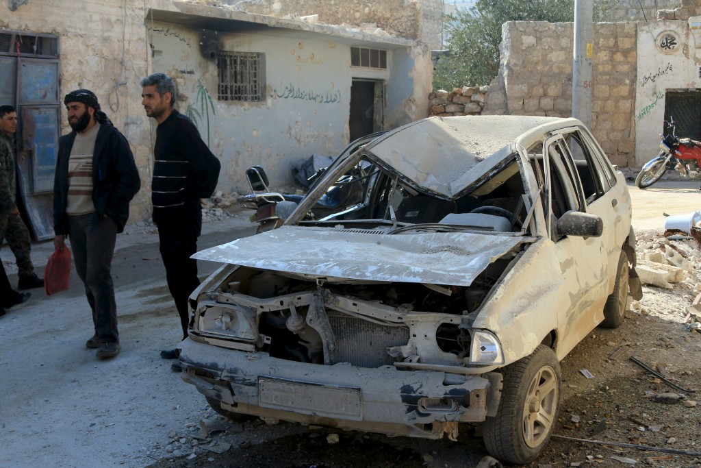 Residents stand near a damaged car in the town of Darat Izza, province of Aleppo, Syria February 28, 2016. REUTERS/Ammar Abdullah