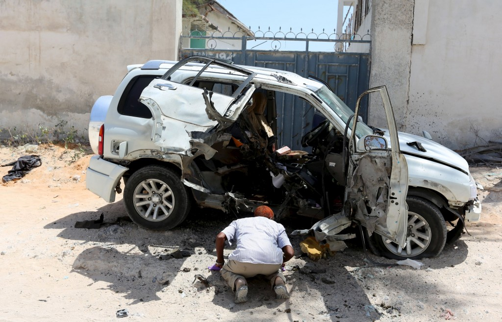 A man looks at a destroyed car after what authorities said was a car bomb attack which killed political advisor of Somali parliament Mohoyadiin Mohamed Haji in the capital Mogadishu February 15, 2016. REUTERS/Feisal Omar