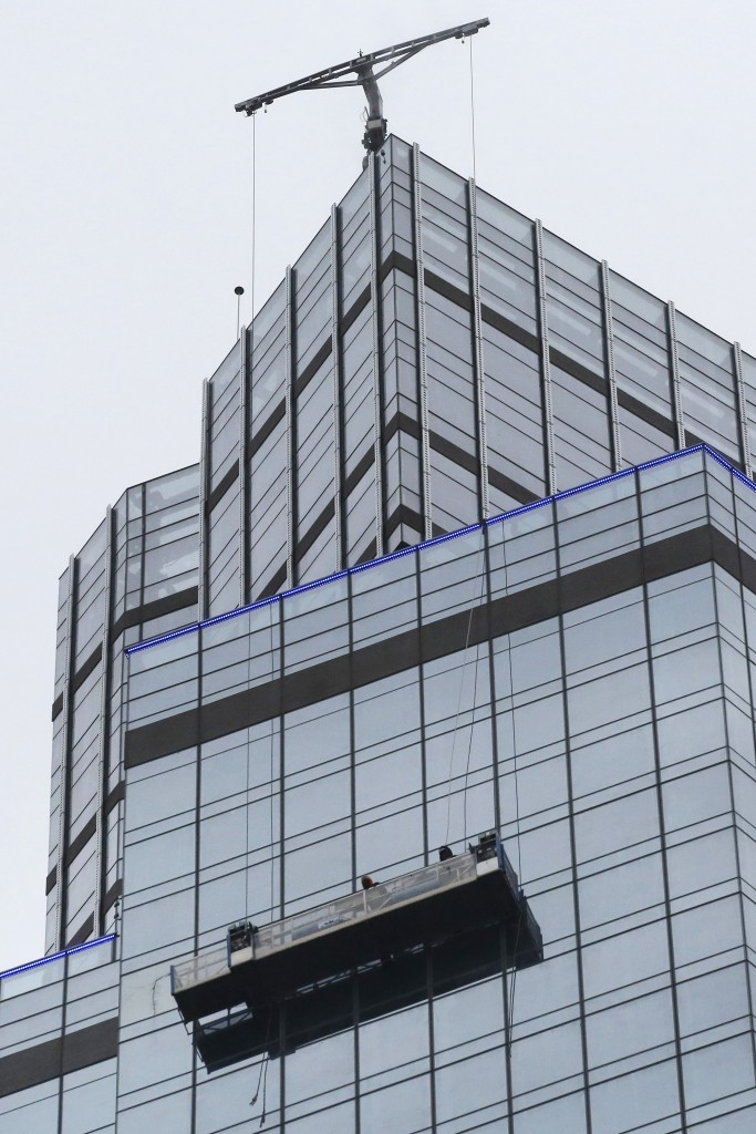 Two window washers are stuck on a scaffold near the top of a Manhattan high-rise building Tuesday, Feb. 23, 2016, in New York. (AP Photo/Mark Lennihan)