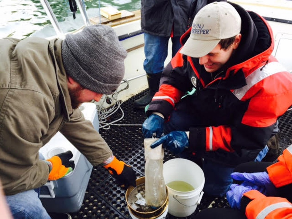 In this March 31, 2015 photo provided by NY/NJ Baykeeper, Mitchell Mickley left, and Justin Procopio process samples of water just collected from New York Harbor near the Statue of Liberty. A report by NY/NJ Baykeeper, says the waterways surrounding New York City are a soup of plastic, ranging from discarded takeout containers down to tiny beads that end up in the food supply. (Sandra Meola/NY/NJ Baykeeper via AP)
