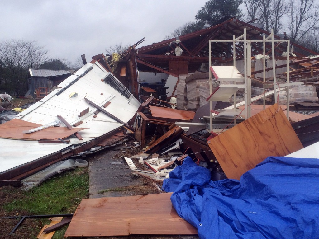 Area residents survey damage to a business off Mississippi Highway 18 in Sylverana, Miss., Monday, Feb. 15, 2016, after severe weather affected south Mississippi. No injuries were reported in the storm. Officials are investigating reports of at least two possible tornadoes that accompanied a line of thunderstorms across central and southern Mississippi Monday. (Ryan Moore/WDAM-TV, via AP)