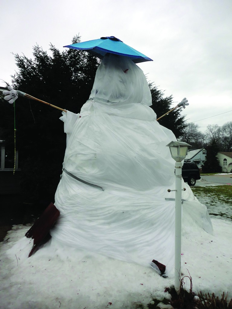 The Fregoe family of Massapequa Park, NY, on Tuesday wrapped their snowman in plastic to protect it from the rain. They hope it lasts into the spring. (Save the Snowman)