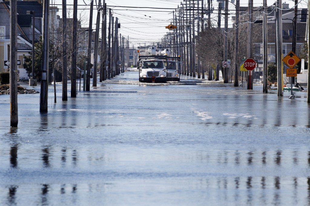 Crews drive utility repair trucks on flooded streets last week Sunday in Sea Isle City, N.J., during the blizzard which hit the area. (AP Photo/Mel Evans)