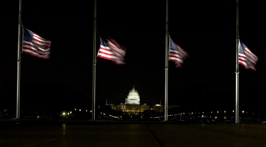 The illuminated Capitol Dome is seen in the distance as flags fly at half-staff around the base of the Washington Monument in Washington, Tuesday, Feb. 16, 2016, in honor of Supreme Court Justice Antonin Scalia who died over the weekend at age 79. (AP Photo/Carolyn Kaster)