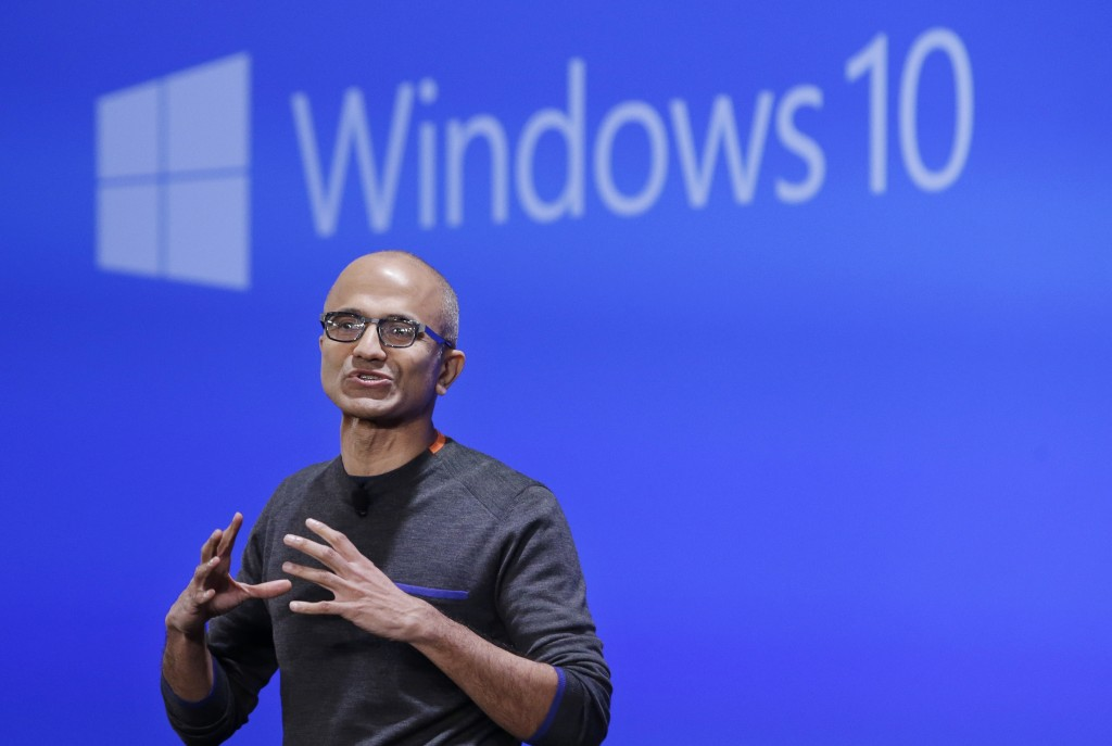 FILE - In this Jan. 21, 2015, file photo, Microsoft CEO Satya Nadella speaks at an event demonstrating the new features of Windows 10 at the company's headquarters in Redmond, Wash. If you're running an older version of Windows, you might suddenly find Microsoft's Windows 10 upgrade already downloaded on your machine. The automatic download, beginning the first week of February 2016, is part of Microsoft's aggressive push to get Windows 10 on as many devices as possible. (AP Photo/Elaine Thompson, File)