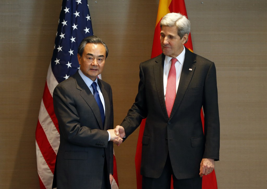 FILE - In this Feb. 12, 2016, file photo, U.S. Secretary of State John Kerry, right, shakes hands with China's Froreign, Minister Wang Yi, during a meeting in Munich, Germany, before the Munich Security Conference. The top diplomats of the U.S. and China meet Feb. 23, in Washington at a fraught time in relations between the two world powers. (AP Photo/Matthias Schrader, File)