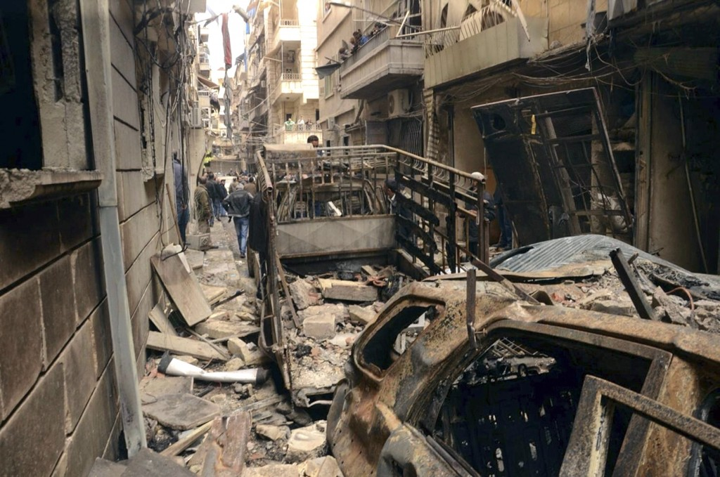 In this photo released by the Syrian official news agency SANA, Syrians gather in a street that was hit by shelling, in the predominantly Christian and Armenian neighborhood of Suleimaniyeh, Aleppo, Syria, April 11, 2015. (AP Photo/SANA)