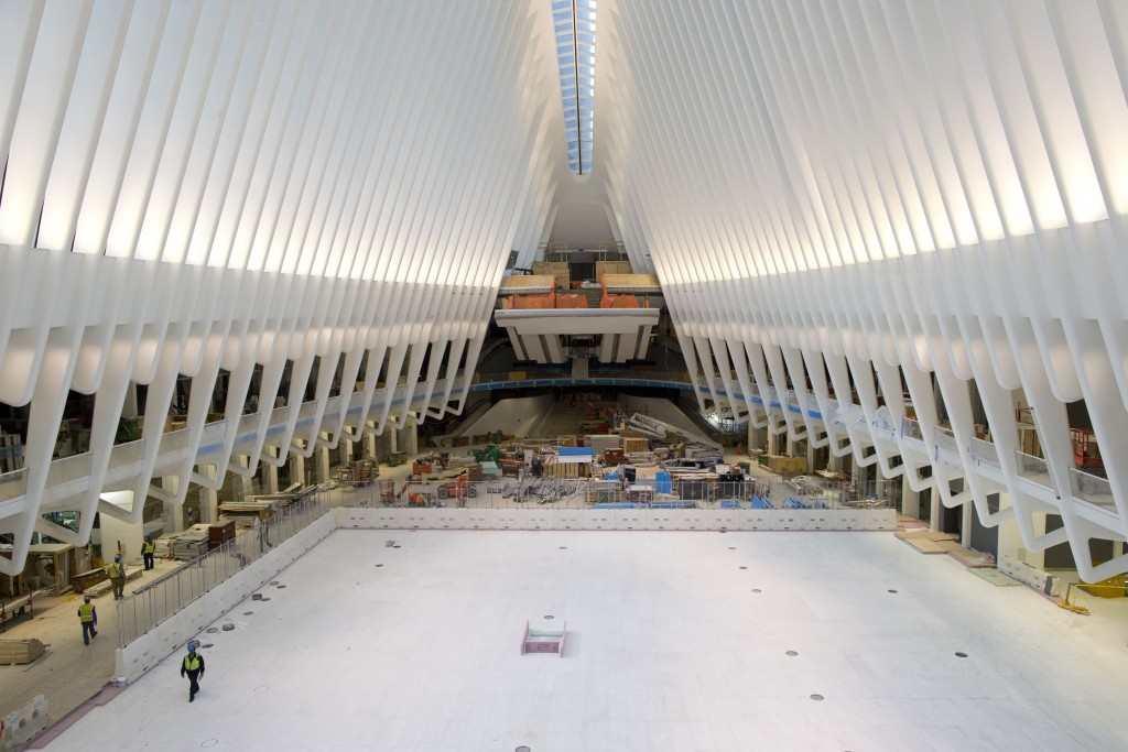 In this Thursday, Feb. 25, 2016 photo, construction workers put the final touches on the World Trade Center transportation hub in New York. The soaring, white transportation hub opening next week at the World Trade Center was designed to evoke a bird in flight, but it is hatching under a cloud. The head of the bi-state agency that controls the hub has blasted it as a symbol of excess with runaway costs approaching $4 billion. (AP Photo/Mary Altaffer)