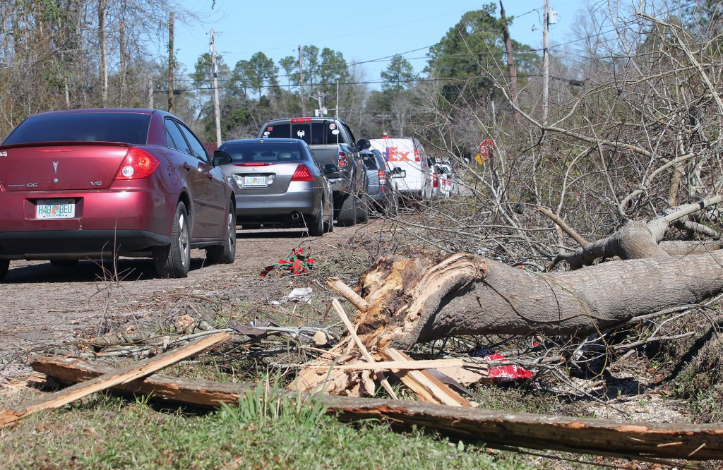 A line of vehicles passes by debris near a home on Jefferson Avenue in Century , Fla., Tuesday Feb.16, 2016. The home was severely damaged by a tornado that struck Monday evening.