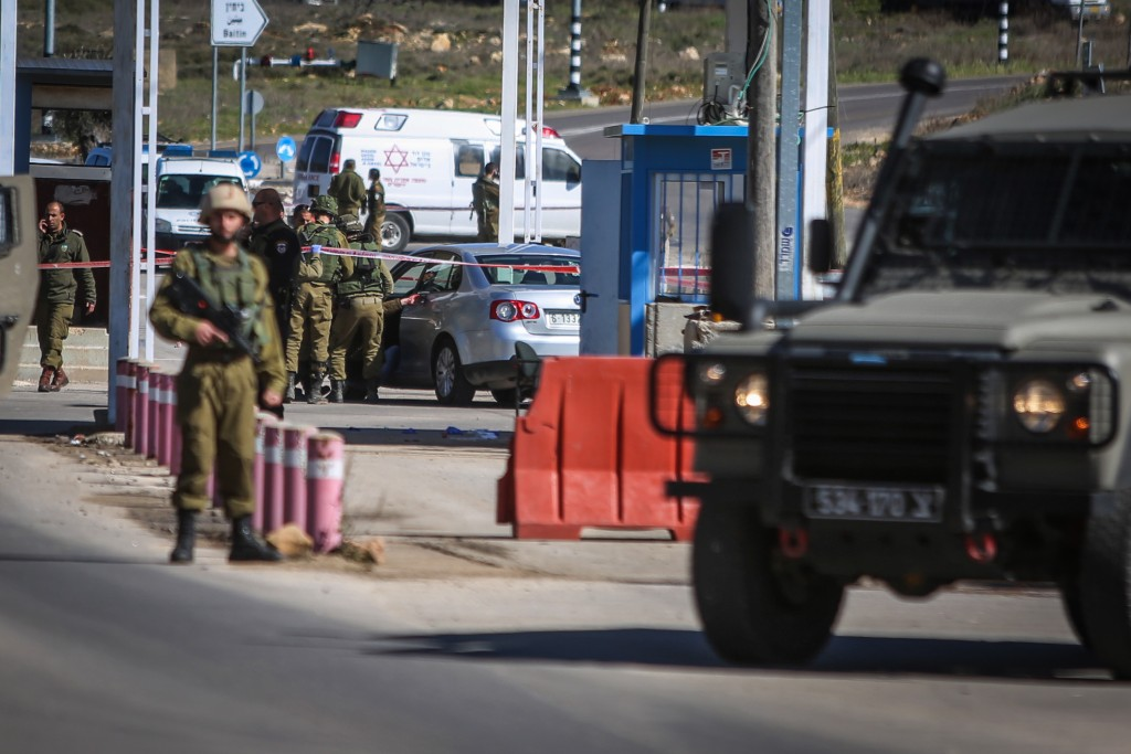Israeli soldiers and security forces stand near the body of a Palestinian attacker, at the scene of shooting attack at a checkpoint near Beit El on January 31, 2016. Photo by Flash90