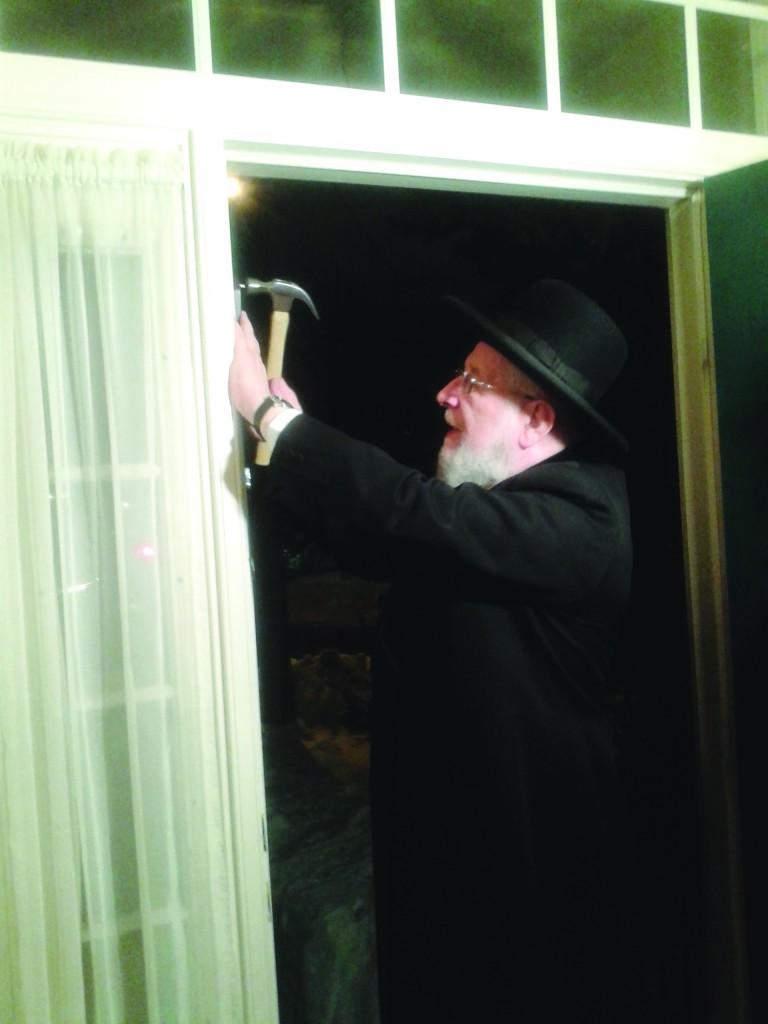 Chief Rabbi of Tel Aviv/Yaffo, Harav Yisroel Meir Lau, affixes a mezuzah on the doorpost of the new Bernard Creeger Bikur Cholim House in Silver Spring, Maryland.