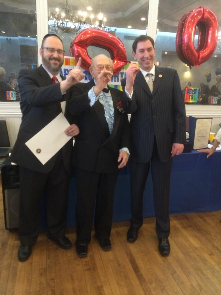 "L-R: State Sen. Simcha Felder, Samuel Saunders and Councilman Chaim Deutsch make the sign of ""100"" Sunday as they celebrate Saunders's 100th birthday in Flatbush. (Office of Sen. Felder)"
