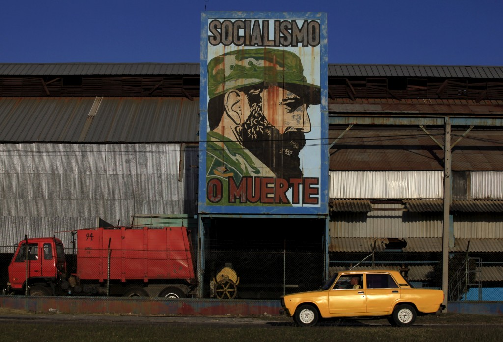 "A man is seen driving a car pass a billboard in a steel factory with the image of former Cuban leader Fidel Castro in Havana March 7, 2016. The sign reads ""Socialism or death"". (Enrique de la Osa/Reuters)"