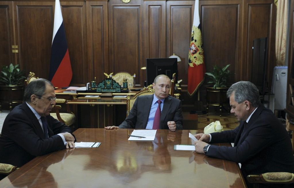 Russian President Vladimir Putin meets with Defense Minister Sergei Shoigu (right) and Foreign Minister Sergei Lavrov at the Kremlin in Moscow, on Monday. (Reuters/Mikhail Klimentyev/Sputnik/Kremlin)