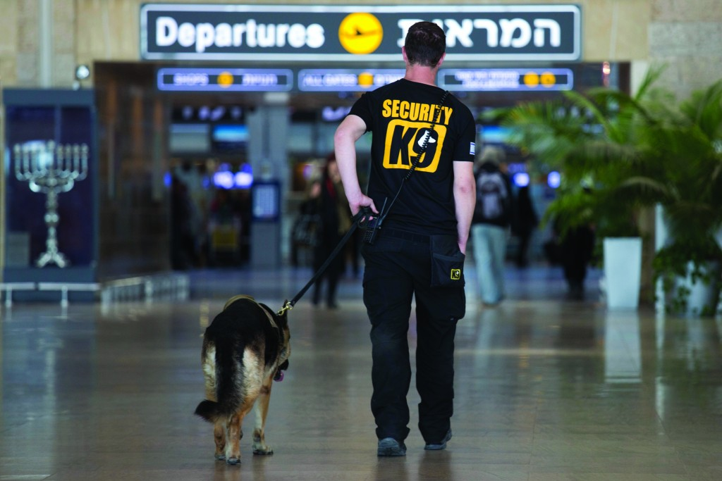 AP Photo/Ariel Schalit An Israeli airport security guard patrols with a dog in Ben Gurion airport near Tel Aviv, Israel, Tuesday. (AP Photo/Ariel Schalit)