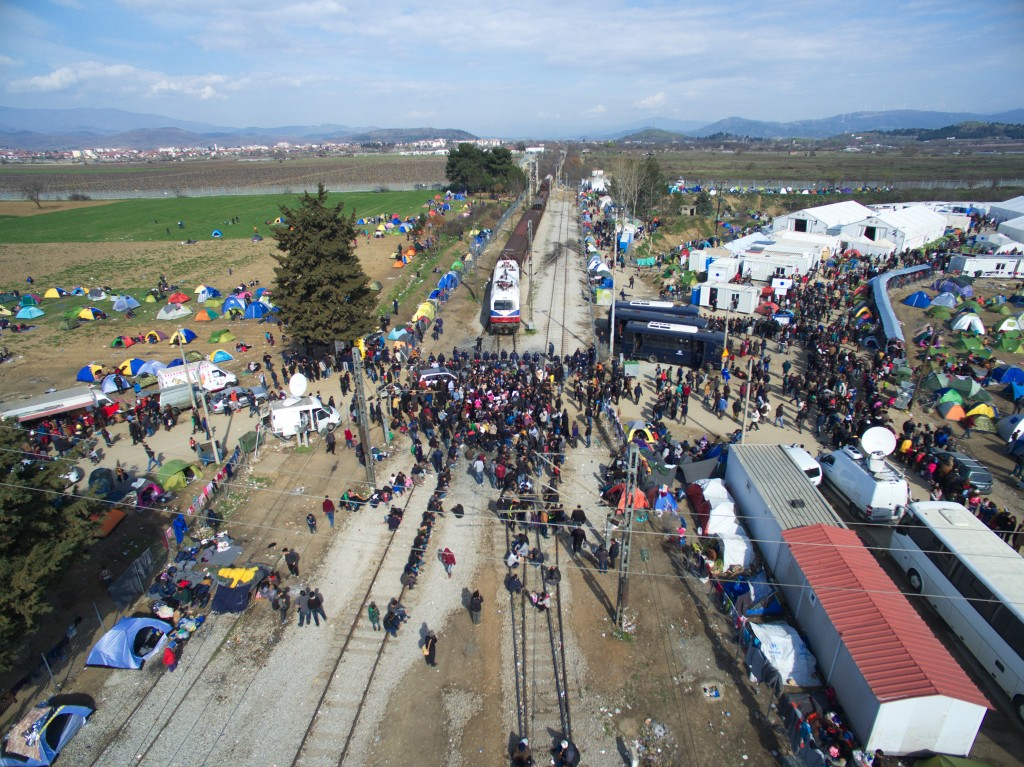 Refugees and migrants block the railway track in front of Greek police cordon as others, right, wait in line to receive food distributed by an NGO at a refugee camp at the Greek-Macedonian border, near the Greek village of Idomeni, Thursday. (AP Photo/Eldar Emric)