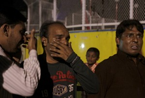 Men mourn the death of their relatives after the blast in Lahore, Pakistan, on Sunday. (Reuters/Mohsin Raza)