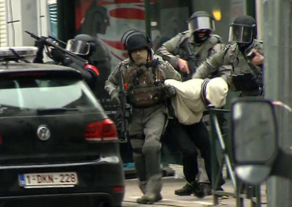In this framegrab taken from VTM, armed police officers escort Salah Abdeslam to a police vehicle during a raid in the Molenbeek neighborhood of Brussels, Belgium, Friday March 18, 2016. The identity of Salah Abdeslam is confirmed Saturday March 19, 2016, by French police and deputy mayor of Molenbeek, Ahmed El Khannouss quoting official Belgium police sources. After an intense four-month manhunt across Europe and beyond, police on Friday captured Salah Abdeslam, the top suspect in last year's deadly Paris attacks, in the same Brussels neighborhood where he grew up. (VTM via AP) BELGIUM OUT