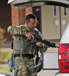 A law enforcement-official stows his weapon after responding to the shooting in Richomd on Thursday. (AP Photo/Steve Helber)