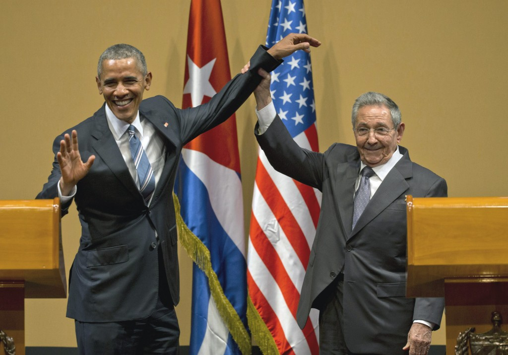 Cuban President Raul Castro, right,  lifts up the arm of President Barack Obama at the conclusion of their joint news conference at the Palace of the Revolution in Havana on Monday. (AP Photo/Ramon Espinosa)