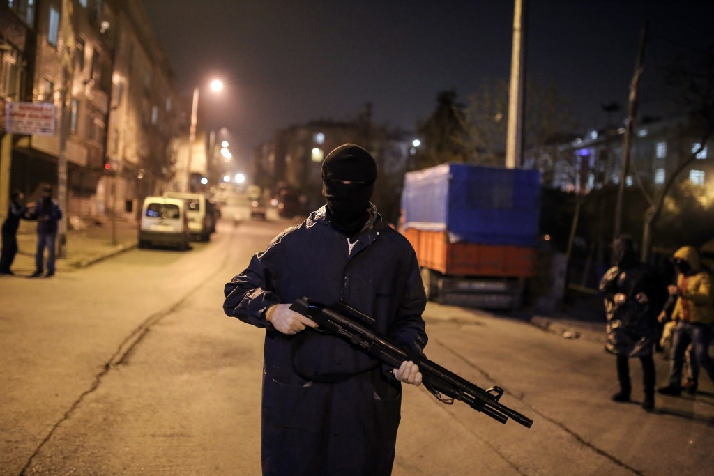 """Masked and armed demonstrators stand near a barricade as they clash with security forces during banned Nowruz celebrations, in Gazi district in Istanbul, Sunday, March 20, 2016. Nowruz, the Farsi-language word for """" new year """", is an ancient Persian festival, celebrated on the first day of spring, March 21, in Central Asian republics, Iraq, Turkey, Afghanistan and Iran.(AP Photo/Cagdas Erdogan)"""