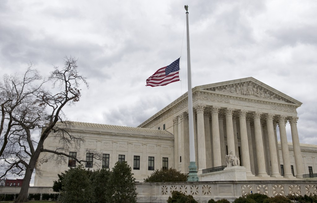 FILE - In this Feb. 25, 2016, file photo, in honor of Justice Antonin Scalia, a flag in the Supreme Court building's front plaza flies at half-staff in Washington. (AP Photo/J. Scott Applewhite, File)