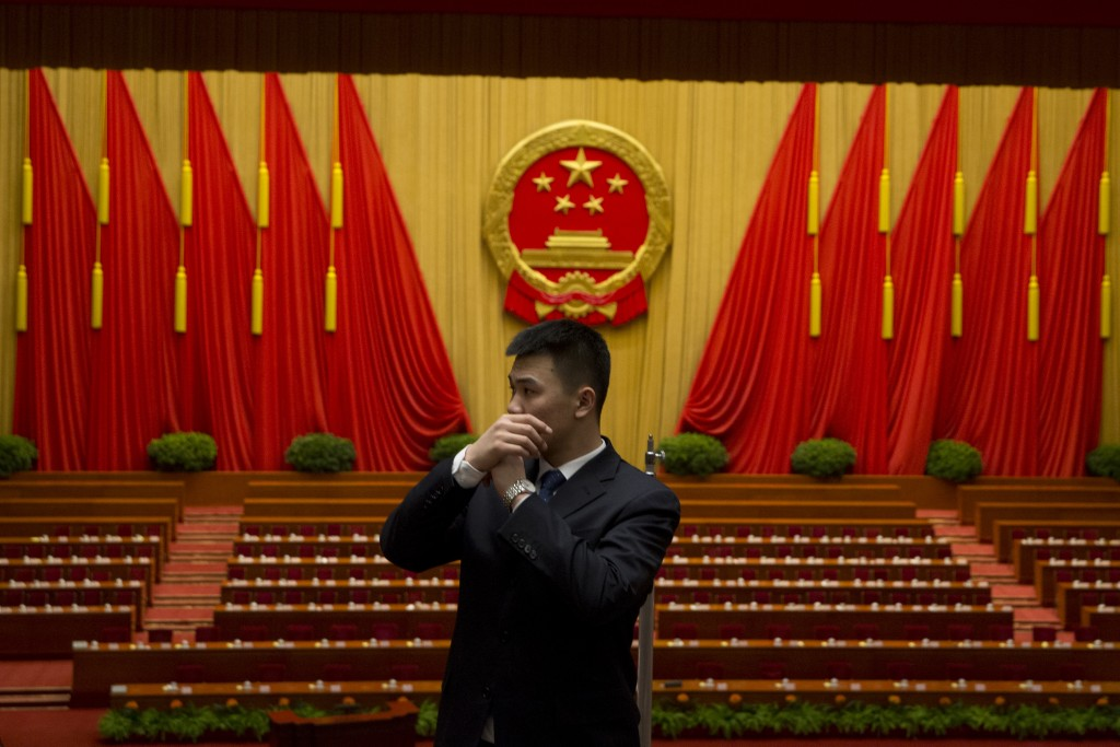 A security guard talks into a microphone attached in his sleeve as he clears the hall after the opening session of the National People's Congress (NPC) at the Great Hall of the People in Beijing. (AP Photo/Ng Han Guan)