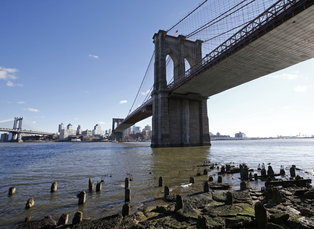 An area between the Brooklyn Bridge, right, and the Manhattan Bridge, upper left, are shown from the East River esplanade, Tuesday, Jan. 19, 2016, in New York. (AP Photo/Kathy Willens)