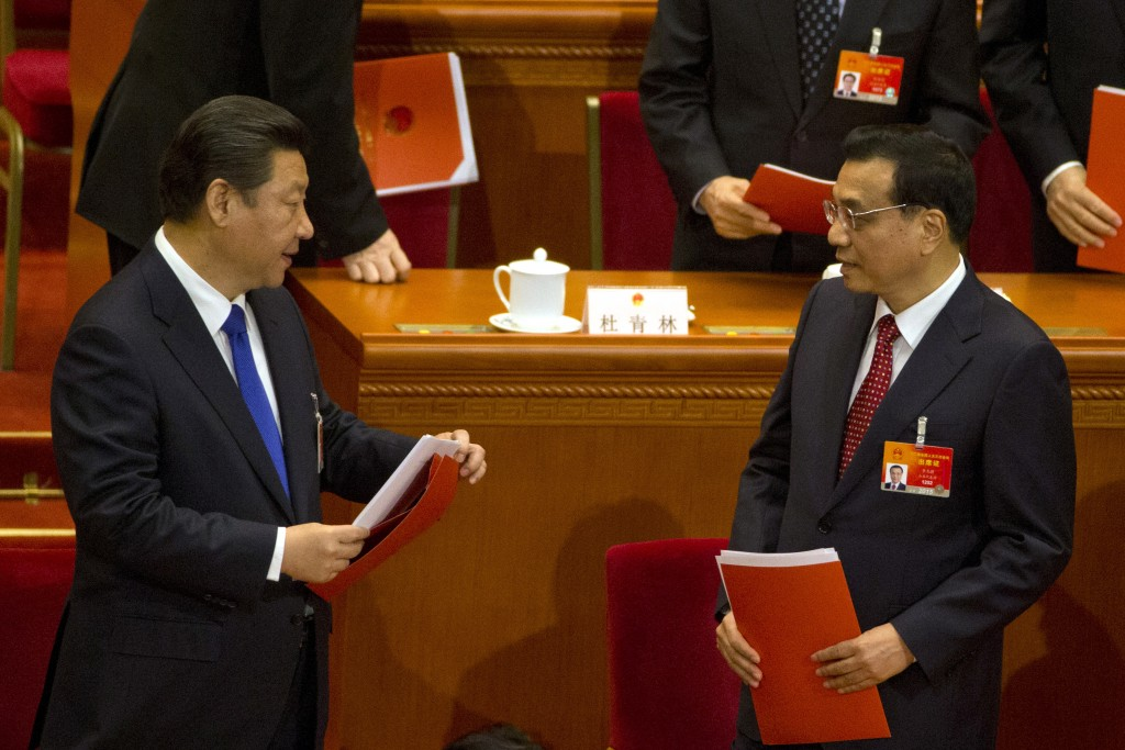 Chinese President Xi Jinping, left, and Chinese Premier Li Keqiang prepare to leave after the closing ceremony of the National People's Congress in Beijing's Great Hall of the People, Sunday, March 15, 2015. (AP Photo/Ng Han Guan)