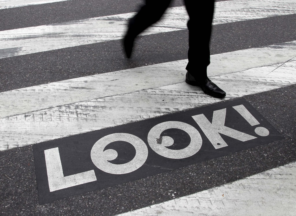 """A pedestrian walks past a """"Look!"""" sign on the crosswalk at the intersection of 42nd St. and 2nd Ave. in New York.  Crossing the street in New York City is complicated: Even when it's one-way, you should look both ways, and stop texting for a few seconds. They're making their point visible with """"LOOK!"""" signs stenciled at 110 of the most dangerous intersections in the city's five boroughs. (AP Photo/Seth Wenig)"""