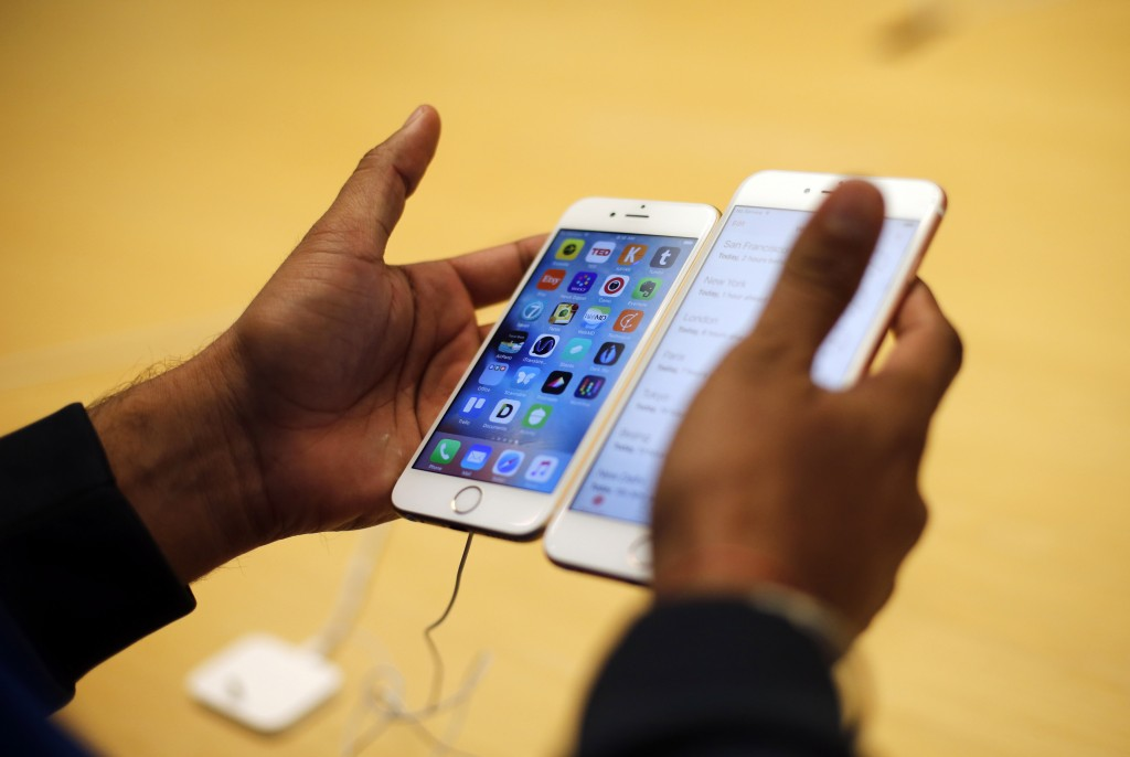 A customer tries out a new Apple iPhone 6S at an Apple store in Chicago. (AP Photo/Kiichiro Sato, File)