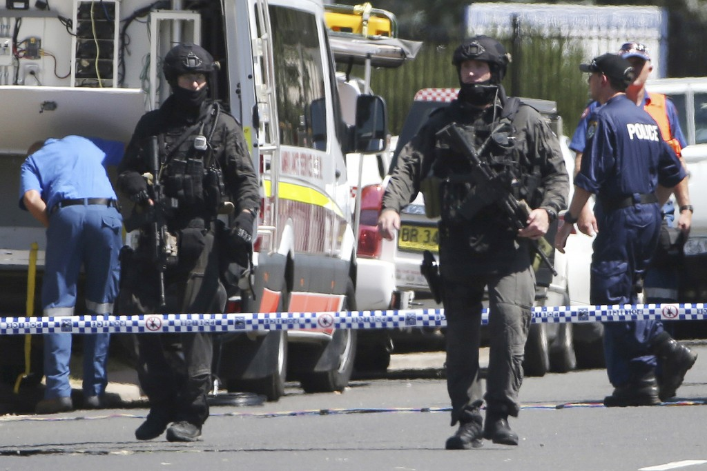 Police Tactical Group officers walk on a cordoned off street of an industrial section of Ingleburn, in suburban Sydney as police respond to a shooting. (AP Photo/Rick Rycroft)