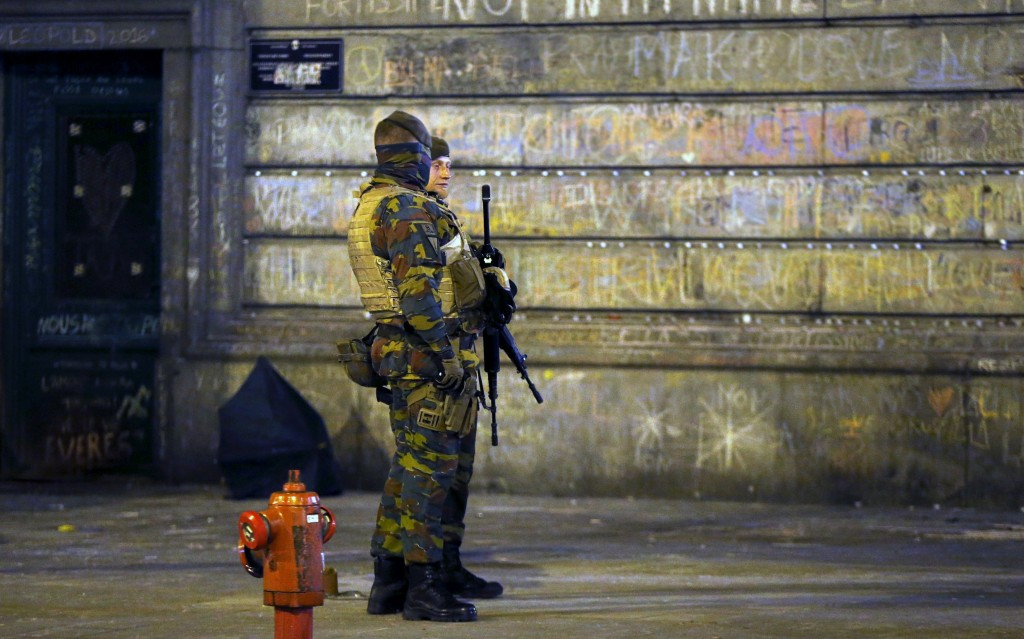 Belgian soldiers patrol, as people pay tribute to the victims of Tuesday's bomb attacks, at the Place de la Bourse in Brussels, Belgium, March 26, 2016.  REUTERS/Francois Lenoir