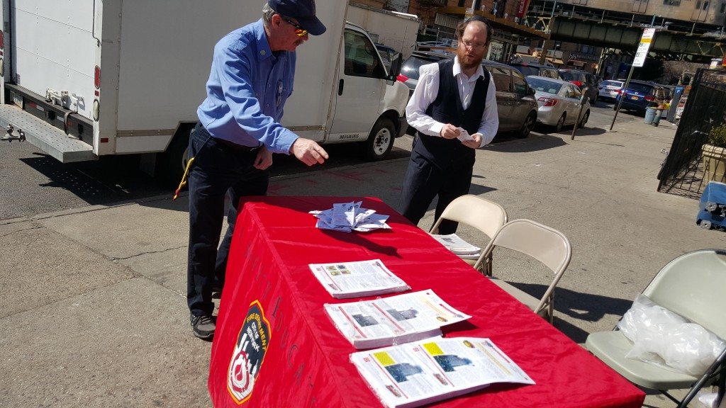 Members of the NYC Mayor's Office and the Fire Department on Wednesday distribute free smoke alarm batteries and fire safety literature in Yiddish in Boro Park. With the changing of the clock, the city recommends using the biannual event to change the batteries of smoke detectors. (Sender Rapaport)