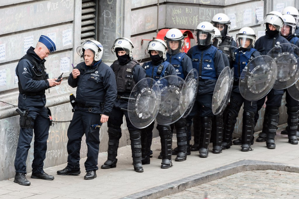 Riot police line up as right wing demonstrators protest at a memorial site at the Place de la Bourse in Brussels, Sunday, March 27, 2016. In a sign of the tensions in the Belgian capital and the way security services are stretched across the country, Belgium's interior minister appealed to residents not to march Sunday in Brussels in solidarity with the victims. (AP Photo/Geert Vanden Wijngaert)