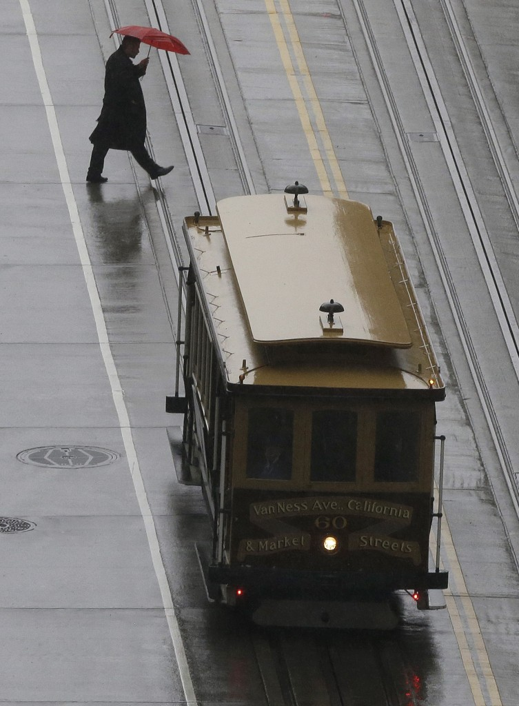 A pedestrian crosses the street behind a Cable Car in San Francisco, Friday, March 4, 2016. The National Weather Service says California's withering winter dry spell will end this weekend as a series of storms move through the state. (AP Photo/Jeff Chiu)