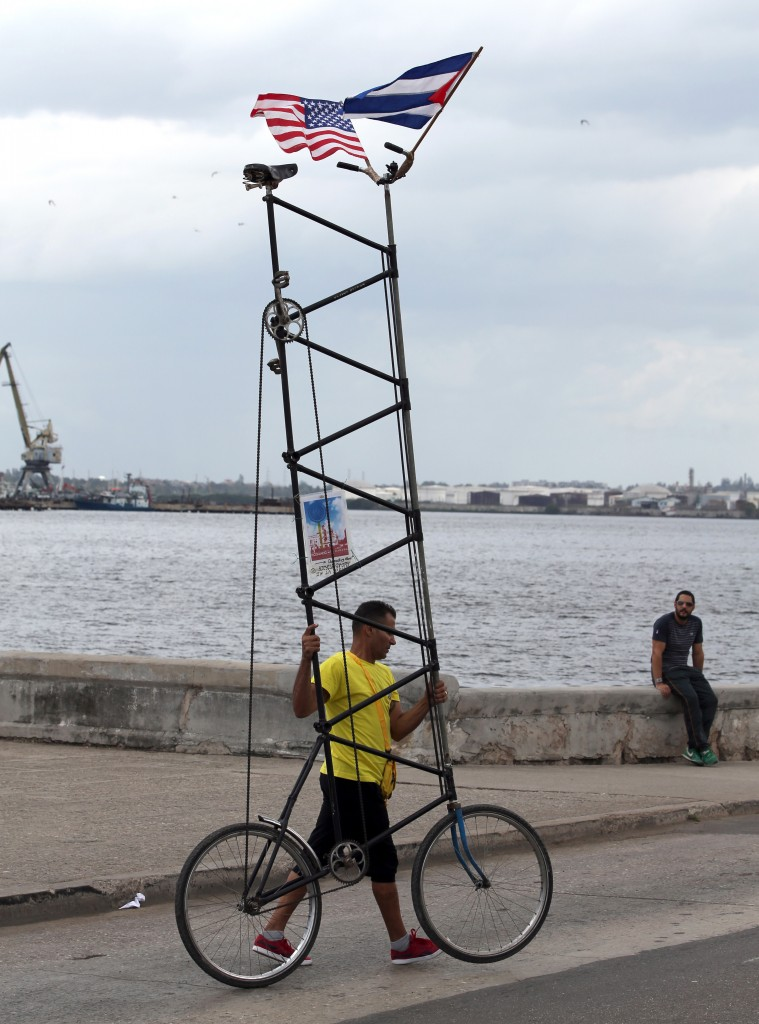 A man pushes his custom-made bicycle decorated with Cuban and U.S. flags along the Malecon Sea Wall in Old Havana, Cuba, on Sunday, ahead of President Barack Obama's arrival. (AP Photo/Enric Marti)