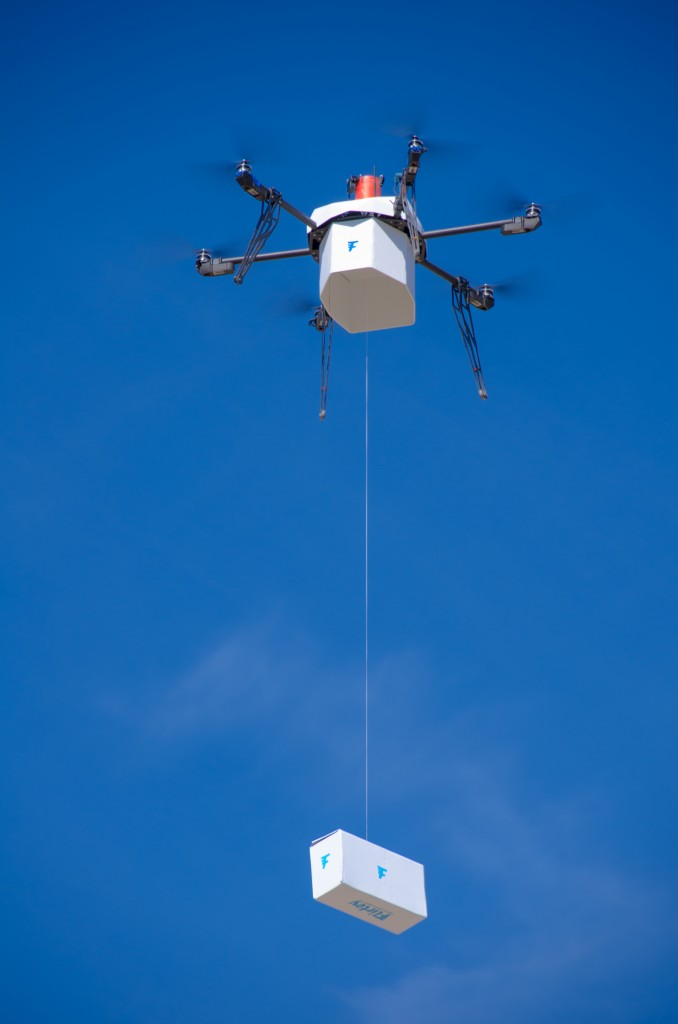 Flirtey, an independent drone delivery company, shows the first fully autonomous, FAA-approved urban drone delivery, a box with bottled water, emergency food and a first aid kit in a residential setting without the help of a human to manually steer it, in Hawthorne, Nev. (Flirtey via AP)