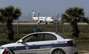 Police stand guard at Larnaca Airport near a hijacked Egypt Air Airbus A320 , March 29, 2016. REUTERS/Yiannis Kourtoglou