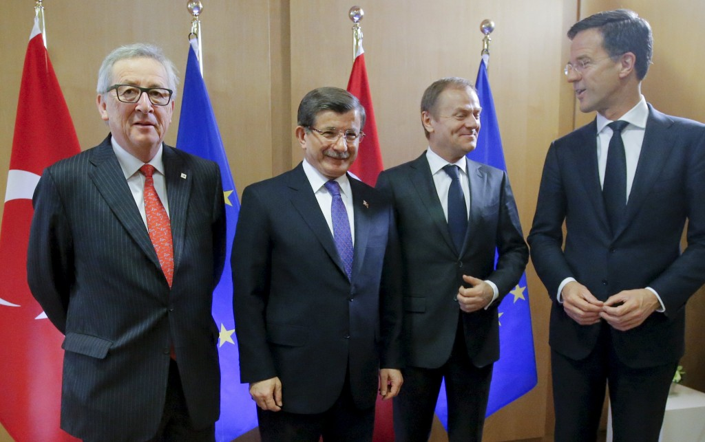 Turkish Prime Minister Ahmet Davutoglu poses with European Commission President Jean-Claude Juncker (L), European Council President Donald Tusk (2nd R) and Netherlands' Prime Minister Mark Rutte (R) during a European Union leaders summit on migration in Brussels, Belgium, March 18, 2016. REUTERS/Olivier Hoslet/Pool