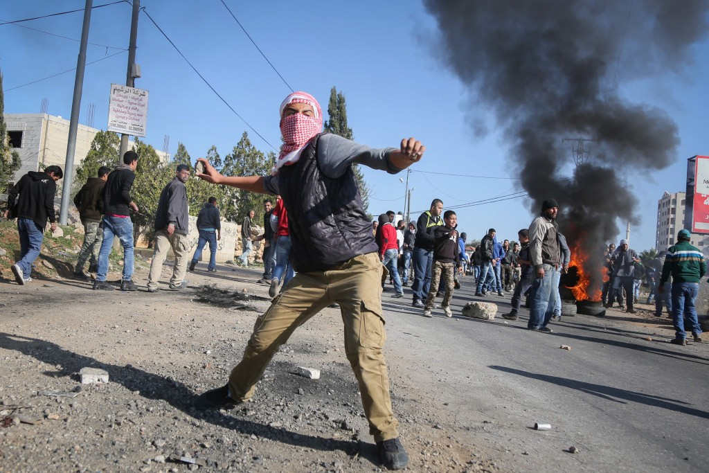 Palestinian terrorists hurl stones during clashes with Israel security forces. (Flash90)